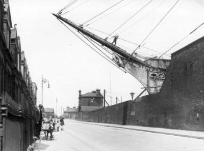 Stewart's Dry Dock on the right and Glen Terrace on the left; the bowsprit of the barque Milverton overhangs the dock wall Manchester Road, 1918. Copyright: Tower Hamlets Local History Library and Archives